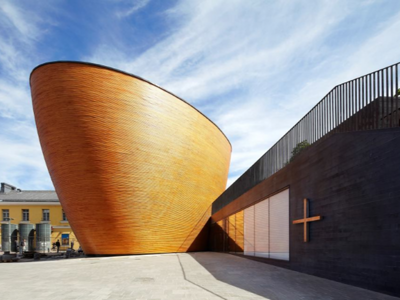 A Curved Wooden Chapel in a Northern Square